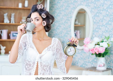 Morning rush. Beautiful woman in hair curlers drinking coffee and holding a clock in her hand