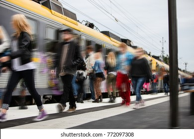 Morning rush hour at the train station with many teenage students hurrying to catch the train to go to school. Blurred for anonymity.