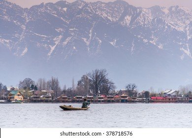 Morning scene of Nigeen lake with the native boat man and the small town behind the mountain range.