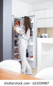 Morning scene. Smiling young woman in the kitchen in front of the refrigerator takes food and laughs