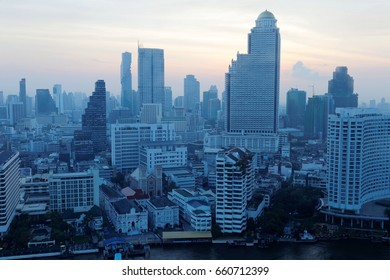 Morning scenery of Bangkok City in bird's eye view ~ Urban skyline of Bangkok in misty twilight, with hotels & office towers by Chao Phraya River & MahaNakhon amid modern skyscrapers under dawning sky