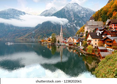 Morning scenery of Hallstatt, a lakeside village in Salzkammergut area of Austria, with a boat cruising on the lake, mountains & houses reflected in the water & colorful autumn forests the on hillside