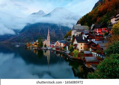 Morgenlandschaft von Hallstatt, einem Seedorf im Salzkammergut, mit einer Schifffahrt auf dem See, Berge & Häuser, die sich im Wasser und bunten Herbstwäldern am Hang widerspiegeln