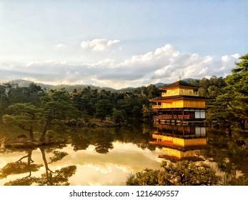 """Morning scenic of Golden Pavilion """"Kinkakuji"""" golden light against in pond."""