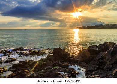Morning sea landscape with rocky coast, menacing skies, reflections and the rays of the rising sun