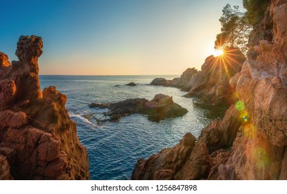 Morning seascape of mediterranean rocky beach in Spain. Amazing view on sea with sunrays behind cliff. Sunrise in Costa Brava. Sea nature landscape