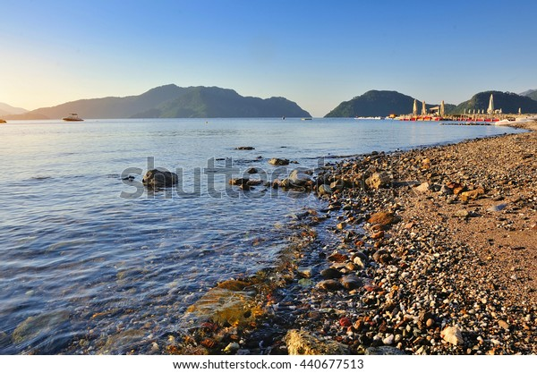 Morning seascape with a pebbly beach and mountains in the background