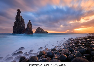 Morning seascape sunrise of Madeira. Rocky shore,  silhouette of two steep cliffs and misty rocks hit by waves. Long exposure. Ribeira da Janela, traveling Madeira island, Portugal.