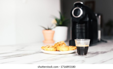 Morning set of a cup with espresso, coffee machine, fresh bakery in a marble background in a kitchen with white walls