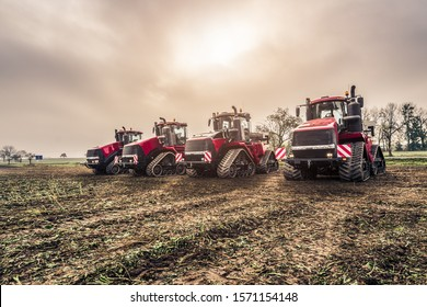 Morning shot of four big track tractors prepared for a working day with dramatic sky. Agricultural photo of tractors prepared for cultivation of field.
