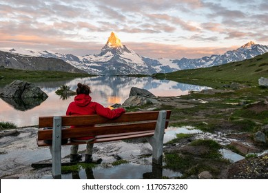 Morning shot of the golden Matterhorn (Monte Cervino, Mont Cervin) pyramid and  blue Stellisee lake. Female tourist enjoying view of early morning Matterhorn mountain is Valais Alps, Switzerland.