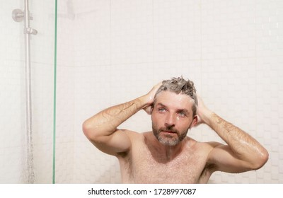 morning shower - lifestyle portrait of young attractive and happy man with beard taking a shower at home washing his hair with shampoo enjoying cheerful in wellness and hygiene concept