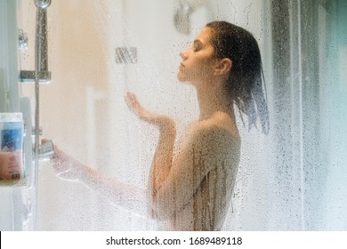 Morning shower.Taking rejuvenating cold shower.Self care moment.Everyday personal hygiene.Unfocused woman showering in glass shower with strong pressure water stream.Focus on drops
