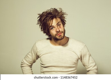 morning. sleepy man with disheveled and uncombed long hair with beard on face in white underwear on grey background, wake up, everyday life, barbershop