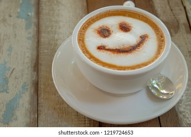 Morning smile cappuccino coffee on wooden table