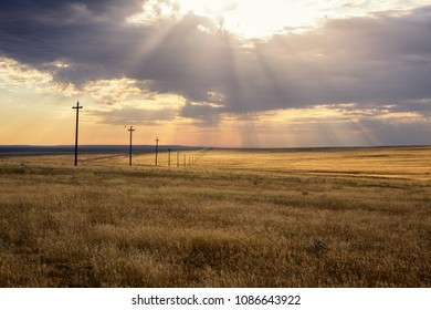 Morning steppe landscape with sun rays over clouds and power-transmission poles