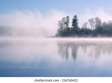 Morning summer nature misty foggy scene: forest with trees surrounded by fog (mist) and reflected on the water surface (lake, river, pond) with a blue sky as a background.