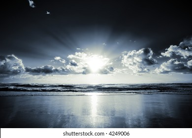 Morning sun bursts through clouds on a beach