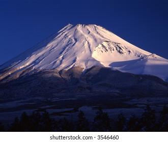 Morning sun illuminating the peak of Mount Fuji on a clear Winter's day
