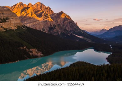 The morning sun lights up Peyto Peak over Peyto Lake, Banff National Park, Canada.,