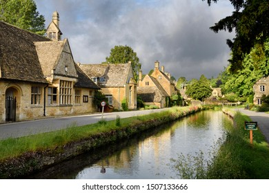 Morning sun on yellow Cotswold limestone buildings of Lower Slaughter on the River Eye with dark clouds Lower Slaughter, Cheltenham, England - June 16, 2019