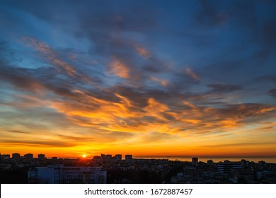 The morning sun rises over the horizon and turns the clouds golden orange. Dawn fire in the sky over a small seaside city. Scenic landscape at sunrise. Beauty in nature.