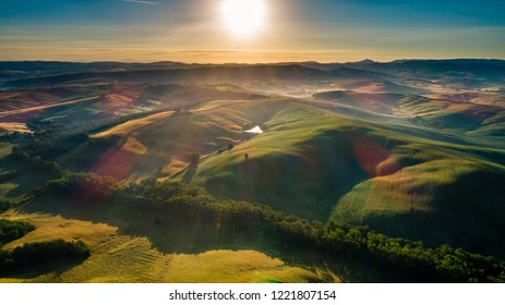 Morning sun shining on green farms and mountains and beautiful landscapes
