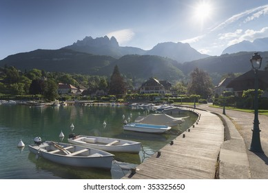 Morning sun shining over the port of Talloires at Lake Annecy in front of the Dents de Lanfon and Lanfonnet mountains in Savoie