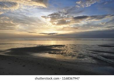 Morning sunlight in cloudy golden blue sky at seashore.  Low tide seashore at dawn.  Seashore at low tide.