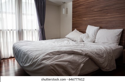 Morning sunlight falling on the bed with a crumpled bedding sheets and pillow through the window. Unmade bed with 3 white pillows and duvet after waking up on wooden background. Messy bed concept