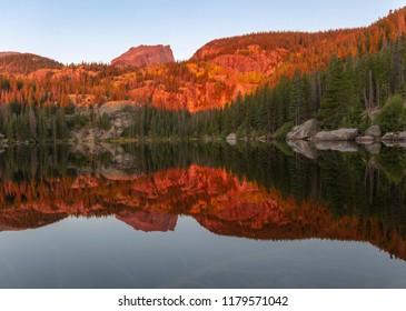 The morning sunlight hits the top of Hallett Peak and the treetops along the banks of Bear Lake in Rocky Mountain National Park outside of Estes Park, Colorado
