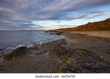 morning sunlight illuminates the shoreline on Guileen Strand, Co.Cork, Ireland