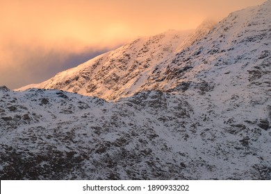 Morning sunlight on Winter snowcapped mountains in the Lake District with beautiful clouds.