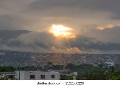 Morning sunlight pours through opening in gray clouds over urban sprawl on east side of Tuxtla Gutierrez the capital city of Chiapas, Mexico
