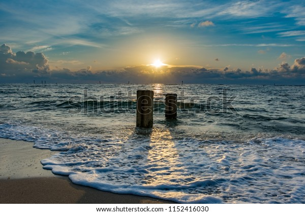 morning sunlight shining between pilons in the sand on a tropical beach