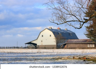 Morning sunlight spreads across a rural acreage covered with a thin layer of snow and illuminated a traditional white barn.