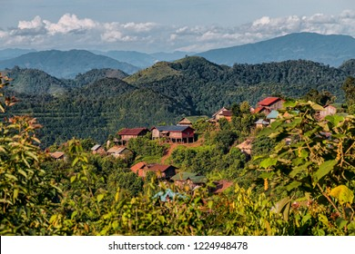 Morning Sunlight View of Traditional Akha Hill Tribe Village on Mountain Top in Nam Ha National Protected Area. Small Ethnic Village in Laotian Rainforest Surrounded by Mountains (Luang Namtha, Laos).