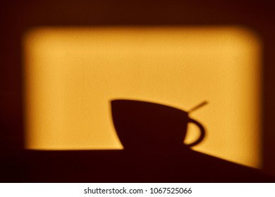 Morning sunny shadow on the wall - A cup with a teaspoon in the cup.