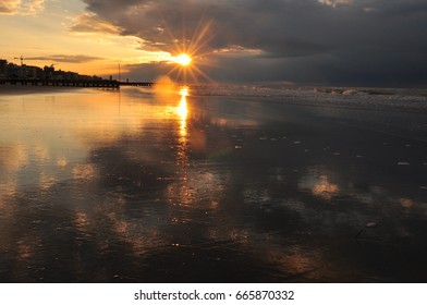 Morning sunrise above seashore with water reflection and sun star effect visible