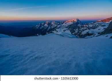 Morning and sunrise around Skuta mountain, Kamnik Savinja alps, Slovenia. Stunning sunrise over mountain alpine landscape, blue and purple sky, dramatic clouds.