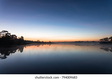 Morning sunrise over the lake with silhouette tree reflect on water surface at Phu Kradaung, national park in Thailand.
