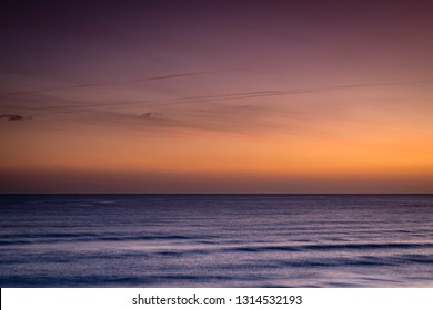 morning sunrise skies over the mediterranean sea near barcelona taken on a clear winter days showing golden and pink hues in the clouds and skie