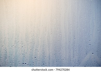 The morning sunrise through the raindrops on the glass. Condensation on Windows in winter. The texture of the water abstraction