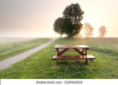 morning sunshine over countryside with table and benches, Holland