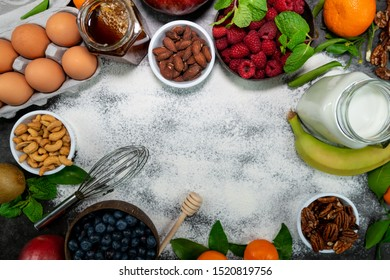 Morning table with different ingredients for cooking breakfast (milk, honey, eggs, tangerines, banana, blueberry, raspberry, almonds, pecans, cashew)