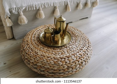 Morning tea in bed. Golden teapot on bedside table. Exotic bedroom interior, boho style