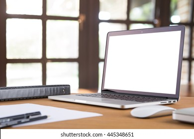 Morning time with warm light. Blank laptop screens on working wooden desk with pen, pencil, document, and text book. business concept.