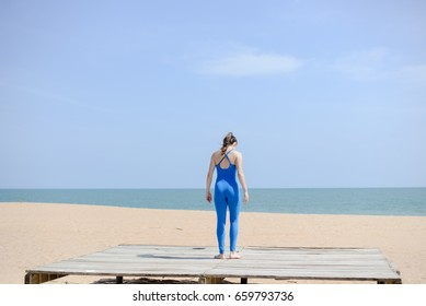 Morning training on the beach. Beautiful female doing workout on sunny blue sky outdoors background. Healthy lifestyle exercises. Back side view of perfect fit shape body