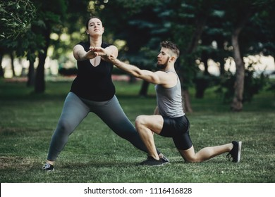 Morning training, sport, weight loss, teamwork and healthy lifestyle concept. Overweight woman doing yoga exercise with personal trainer support. Side or lateral lunge fat burning exercise