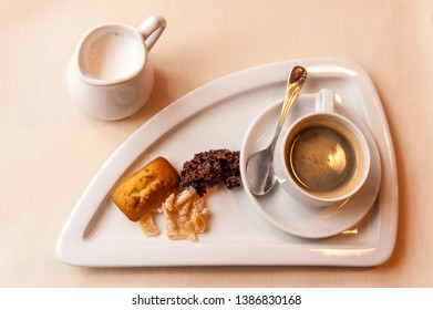 Morning tray with espresso cup, sweets and jug of milk viewed from above